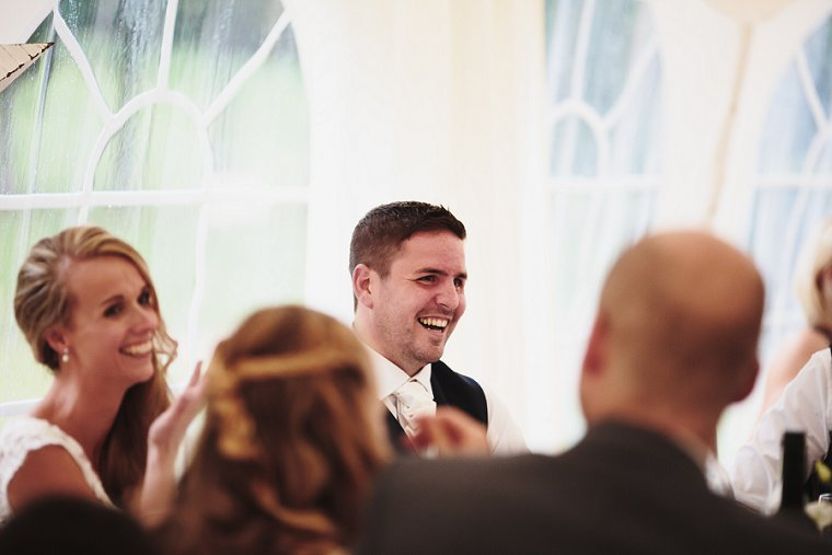 Groom laughing during mother of the brides speech