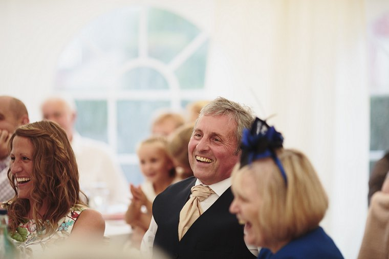 Father of the groom laughing during mother of the brides speech