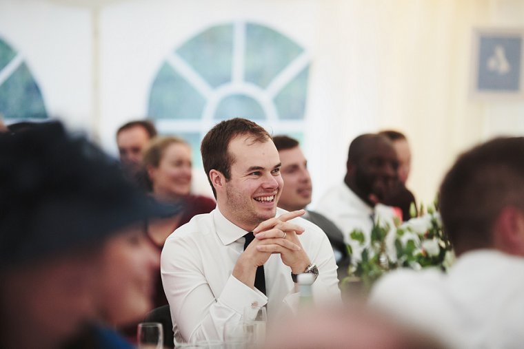 Wedding guest laughing during grooms speech at Squerryes Court Wedding