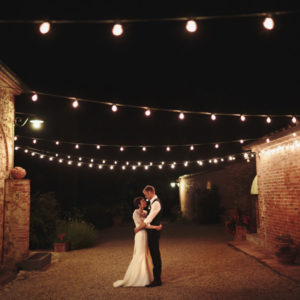 Megan and Ian posing underneath some string lights at night time after their wedding in Tuscany