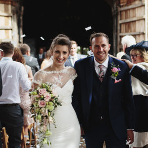 Andy and Chloe walking down the aisle after their wedding service at Ratsbury Barn in Kent