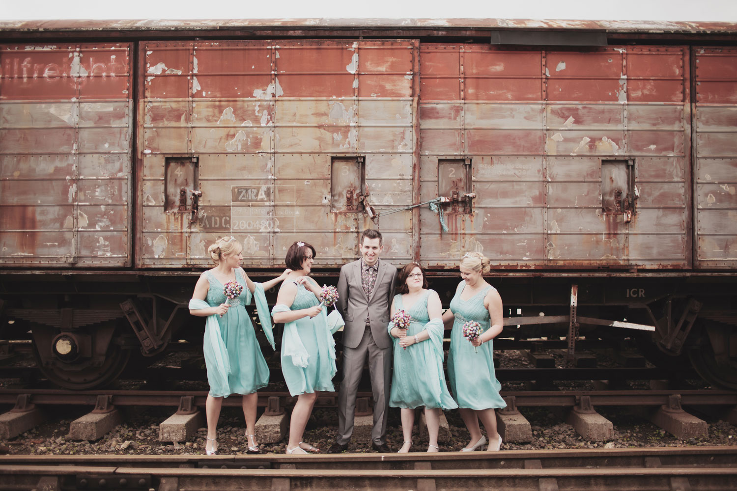 Groom posing for group photo with bridesmaids