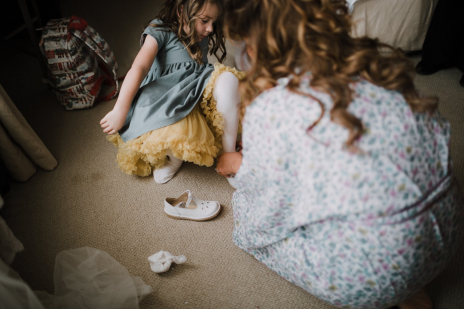 Bride helping her flowergirl put her shoes on