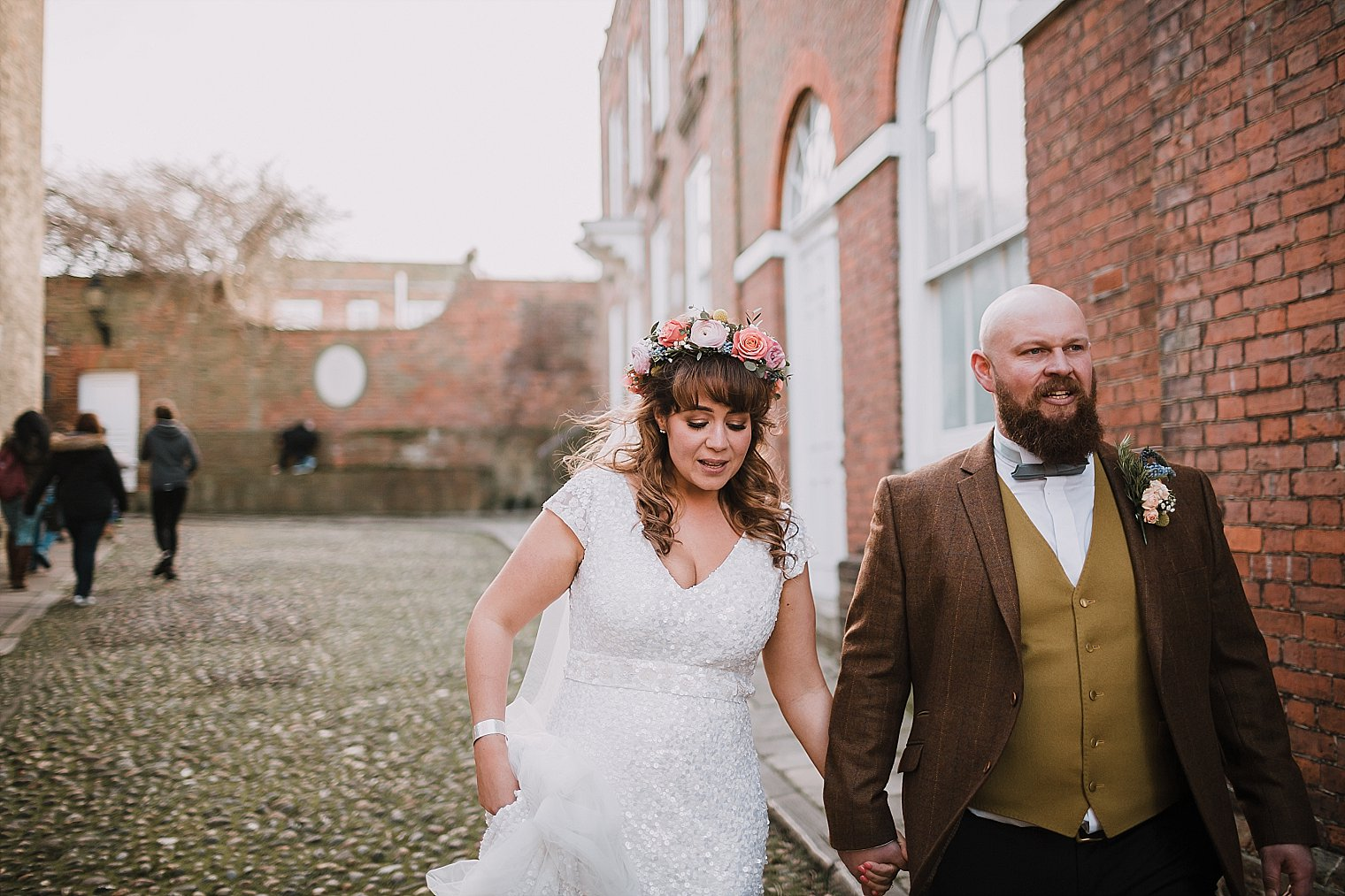 Bride and groom in Rye holding hands during their wedding portraits