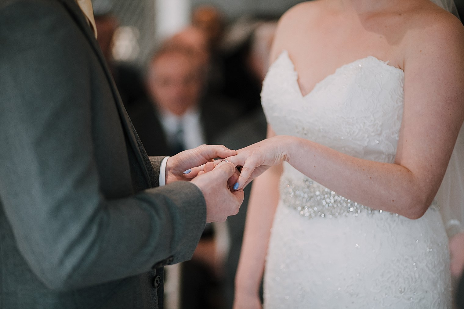 Groom placing wedding ring on the bride