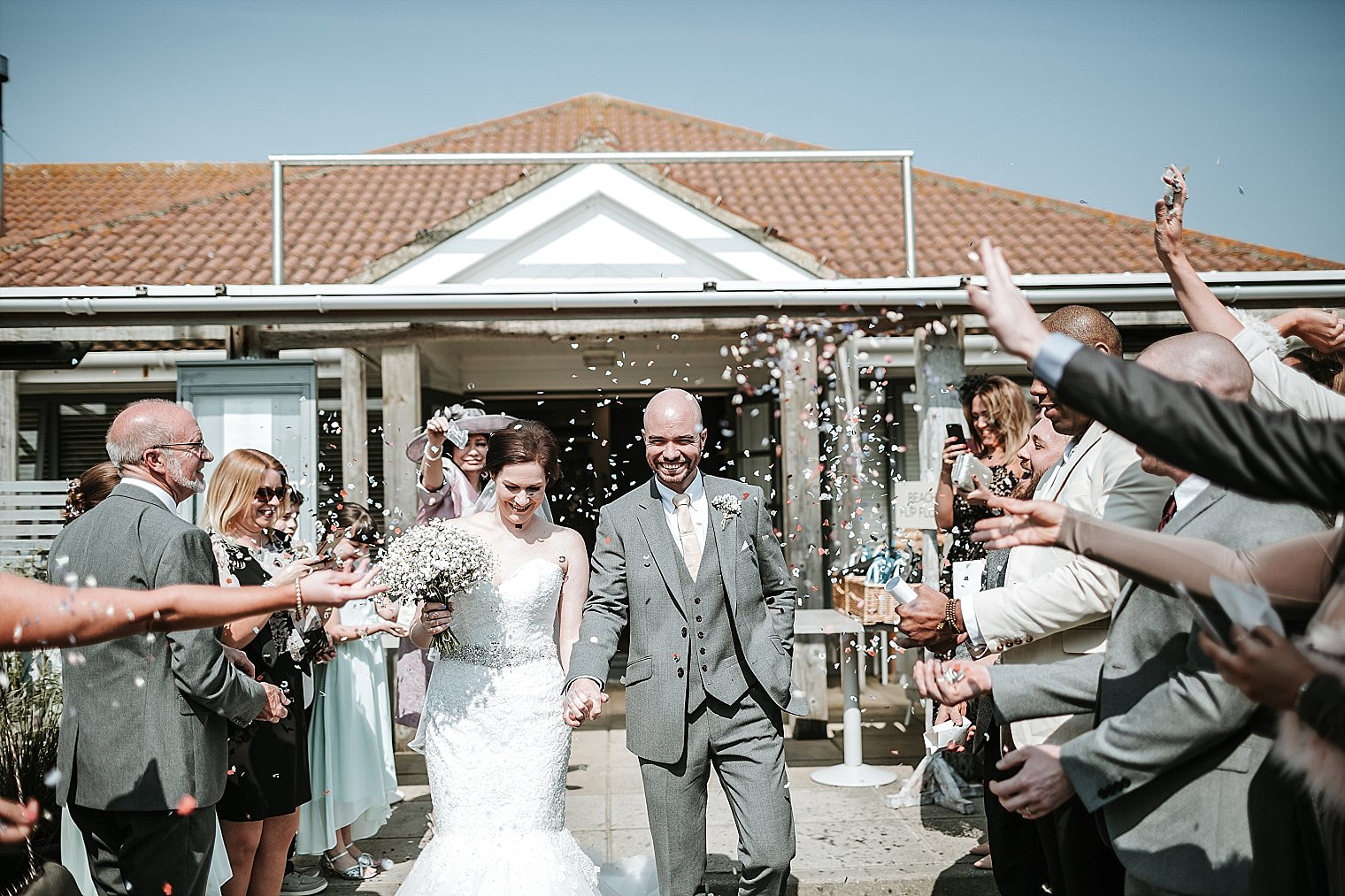 Bride and Groom having confetti thrown on them outside The Gallivant in Camber