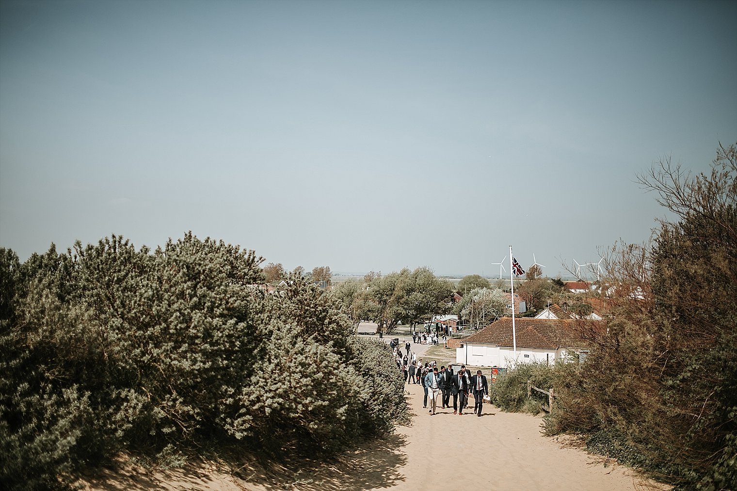Wedding guests walking towards the drinks reception on Camber Sands