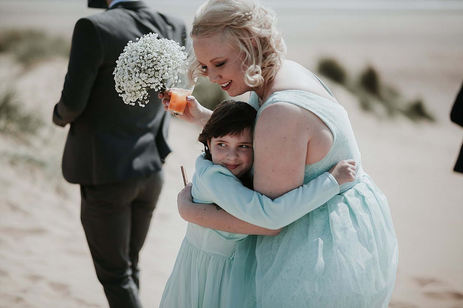 Bridesmaid and flower girl hugging