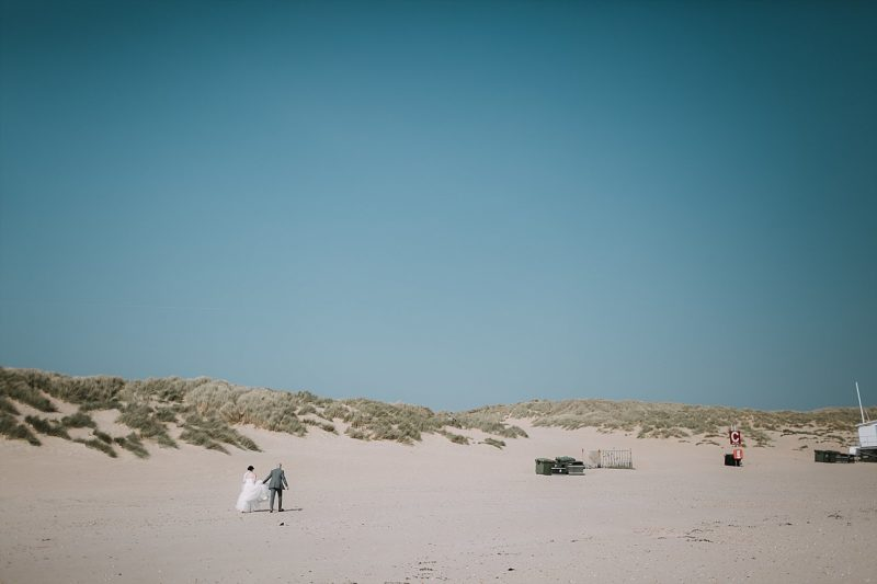 Wedding couple walking across Camber Sands at The Gallivant