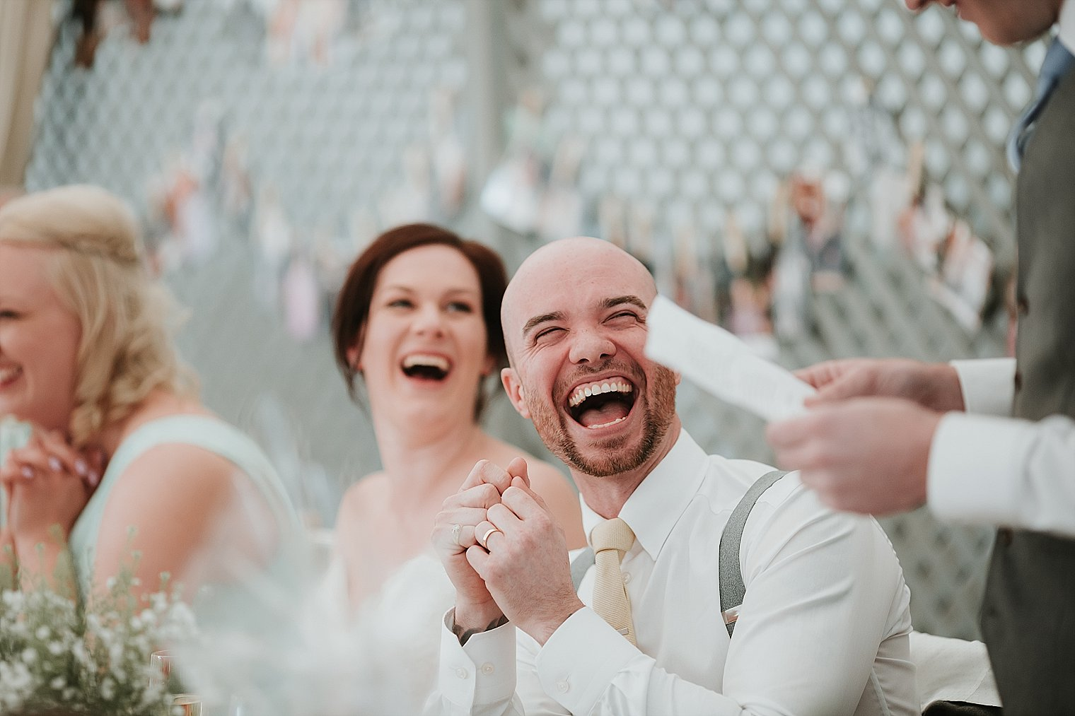 Groom laughing during best mans speech