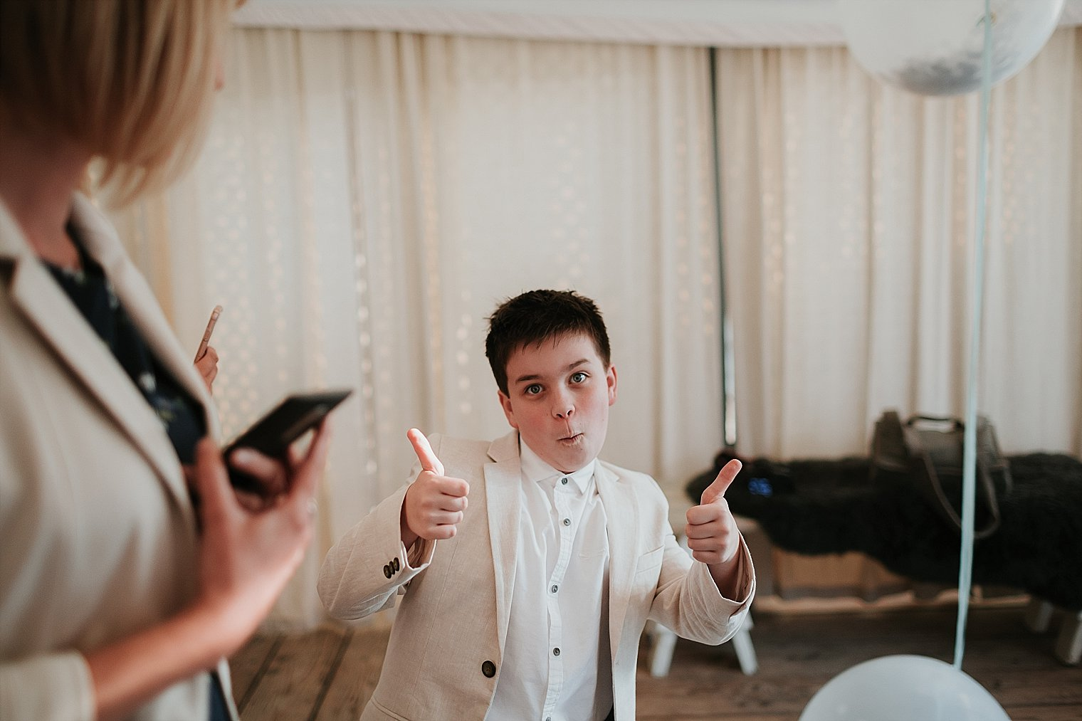 Young wedding guest giving the thumbs up