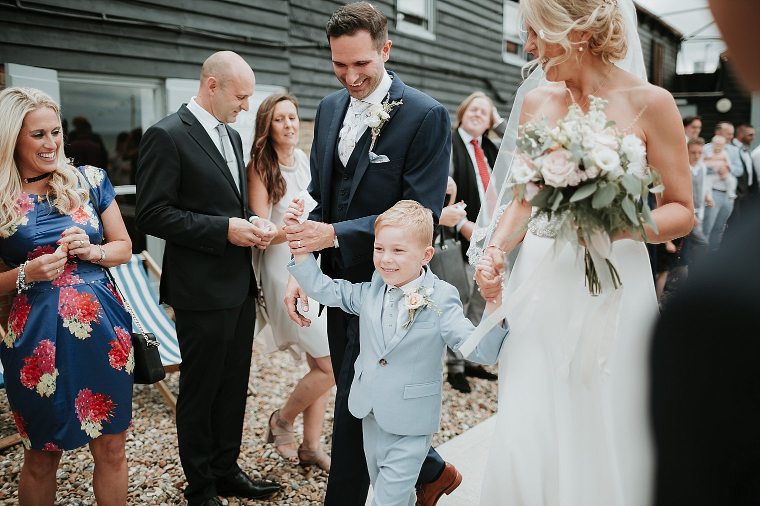 Bride and Groom with their son walking through confetti at Whitstable Brewery Bar