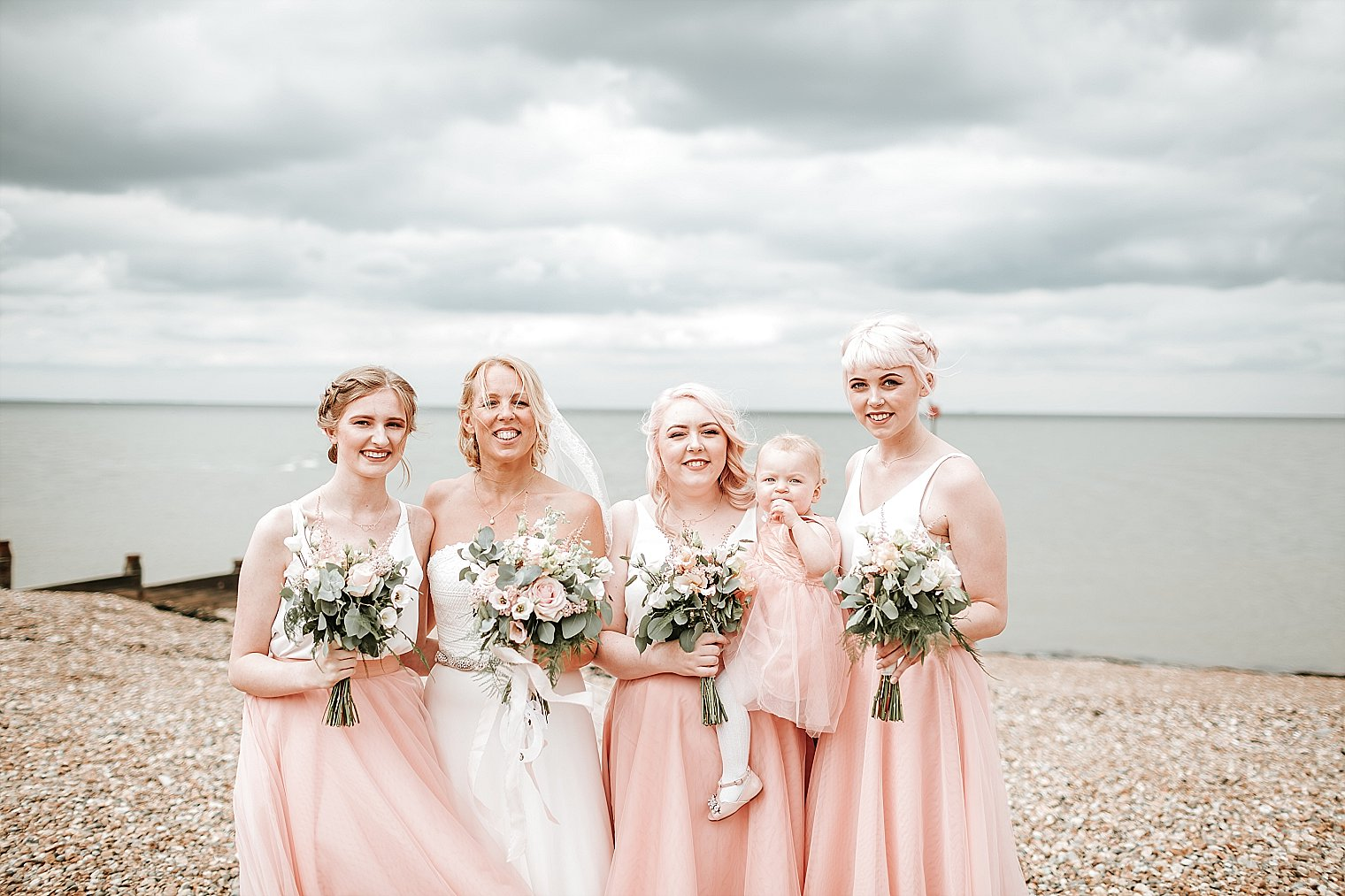 Bride and Bridesmaids posing on the beach at Whitstable