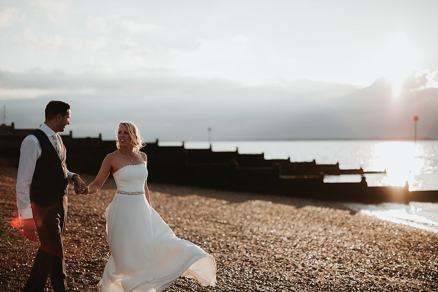 Bride and Groom walking on pebbles at Whitstable beach