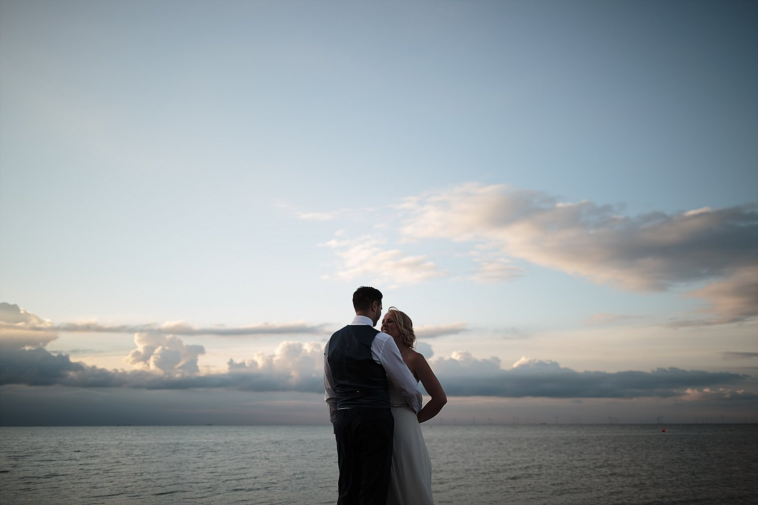 Bride and Groom posing against blue sky At East Quay Wedding venue