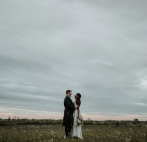 Bride and Groom posing for wedding portraits in a field at Cripps Barn