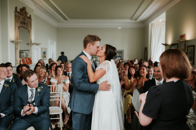 Bride and groom sharing first kiss after their wedding ceremony