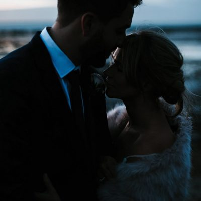 Bride and Groom hugging on Whitstable beach at sunset