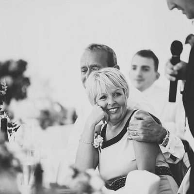 Mother of the groom smiling during her sons wedding speech